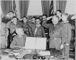 Photograph of President Truman in the Oval Office receiving a report on the accomplishments of the Boy Scouts from a delegation of Eagle Scouts, who are giving him the Boy Scout salute. (National Archives and Records Administration)